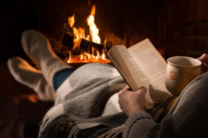 Woman reads book near fireplace